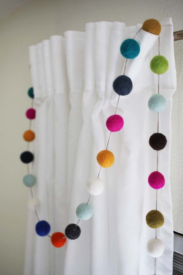 Don't buy a felt ball garland when they are SO easy to make! Use felt balls and embroidery floss to add colorful and fun to an unexpected spot in your home.