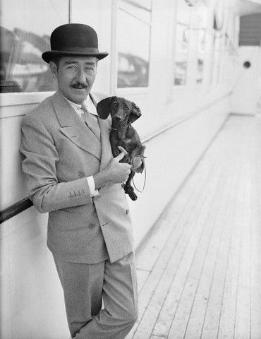 0 adolphe menjou holding in his arms his dachshund on a boat