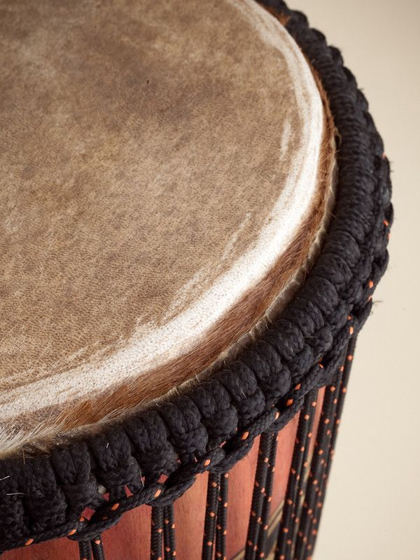 The Mahogany Djembe Drum is a Nigerian hand drum. First, Akeem carves the mahogany wood to create a unique traditional design. Then he paints the wood to add color to the design. Then he stretched the