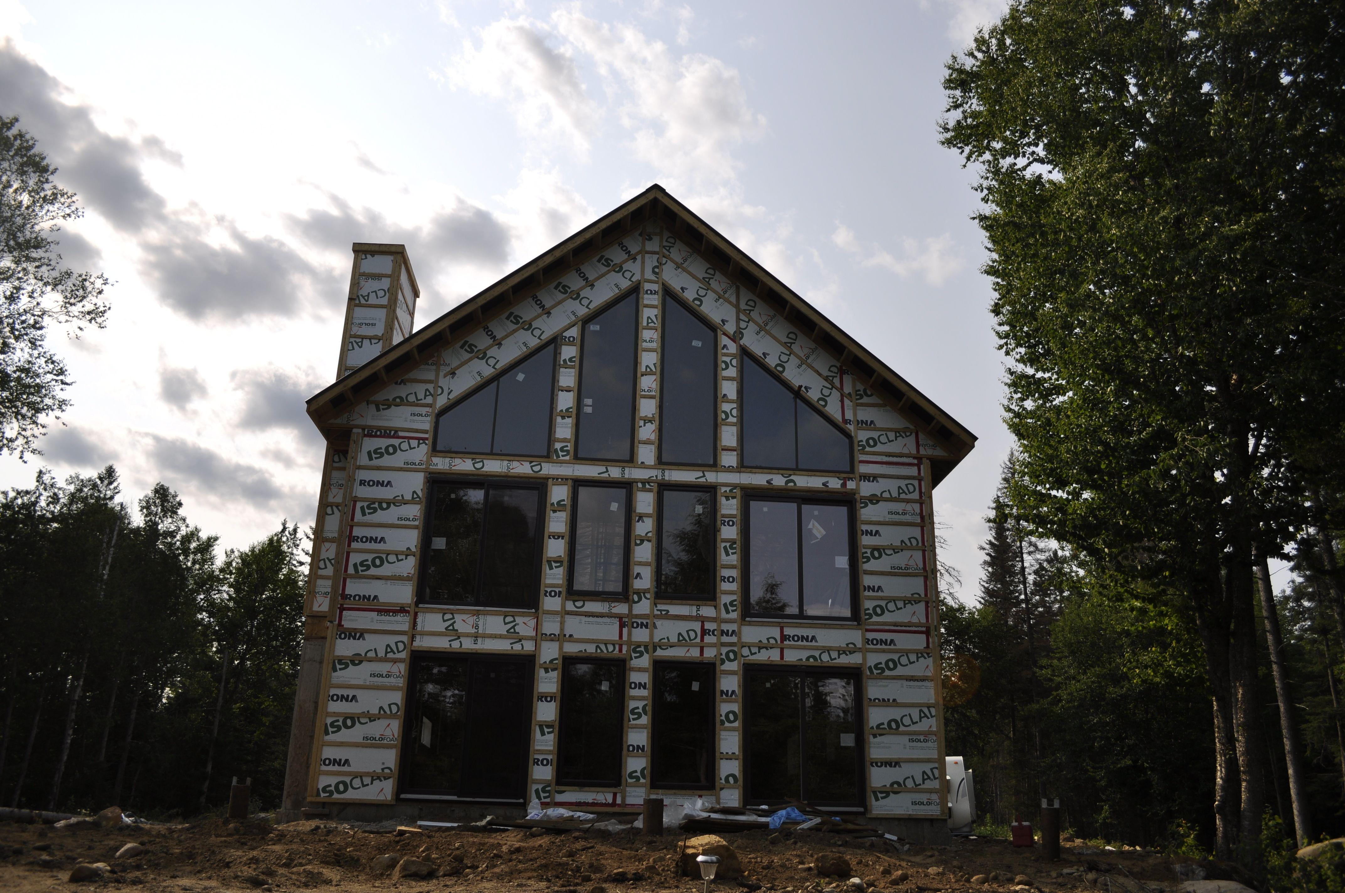 Structure de maison chalet avec mur de vitre et intérieur cathédrale