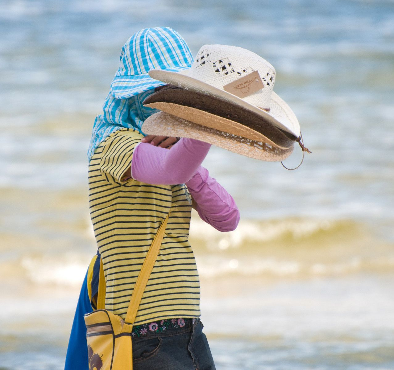Woman selling hats at the beach in Hua Hin, Thailand, in