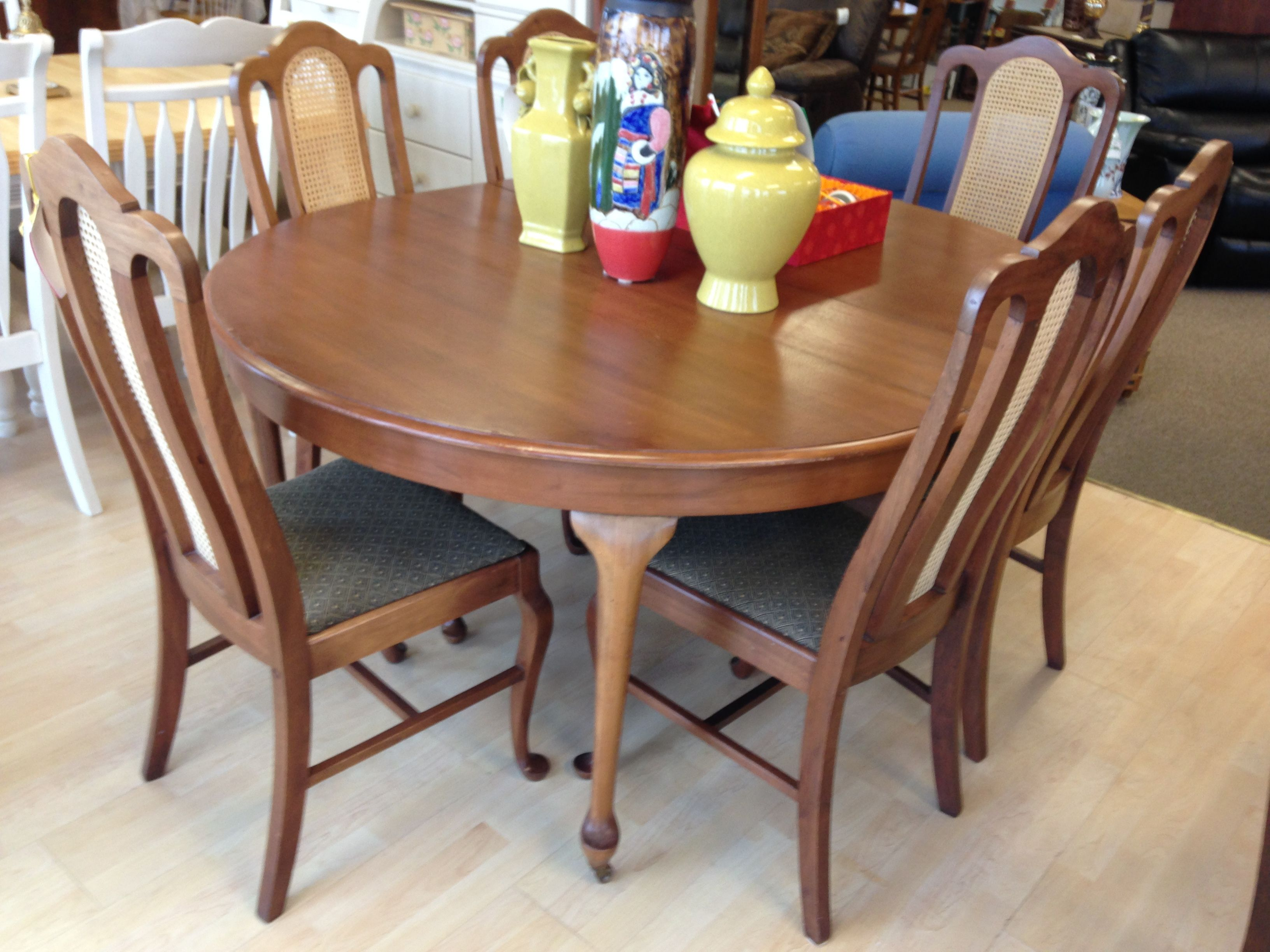 Vintage walnut table with six chairs and two leaves is on wheels