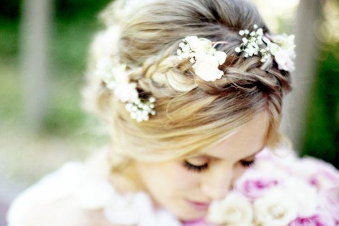 romantische Brautfrisur mit Zopf und Blumen geschmückt