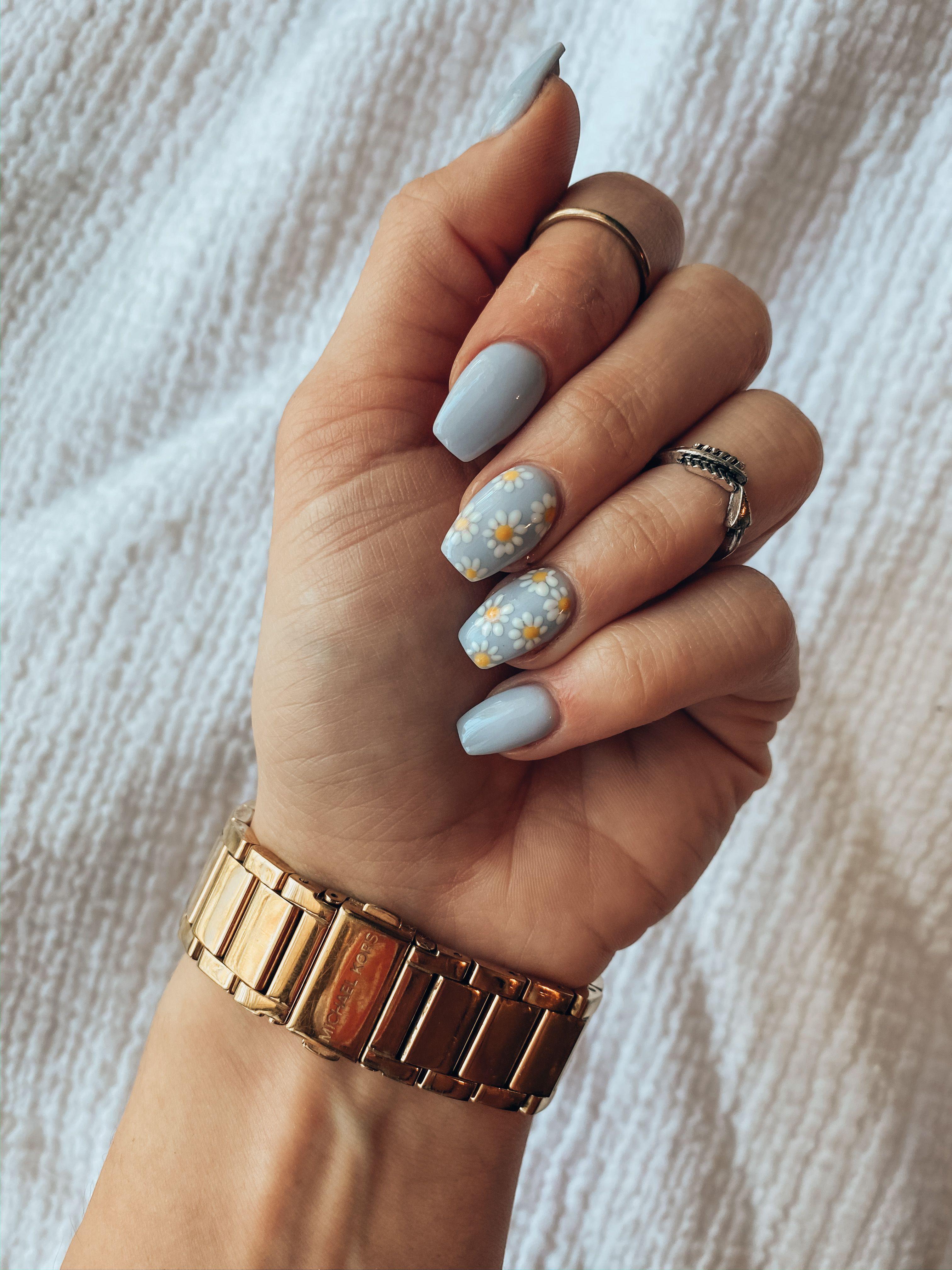 Light blue acrylic nails with daisy design