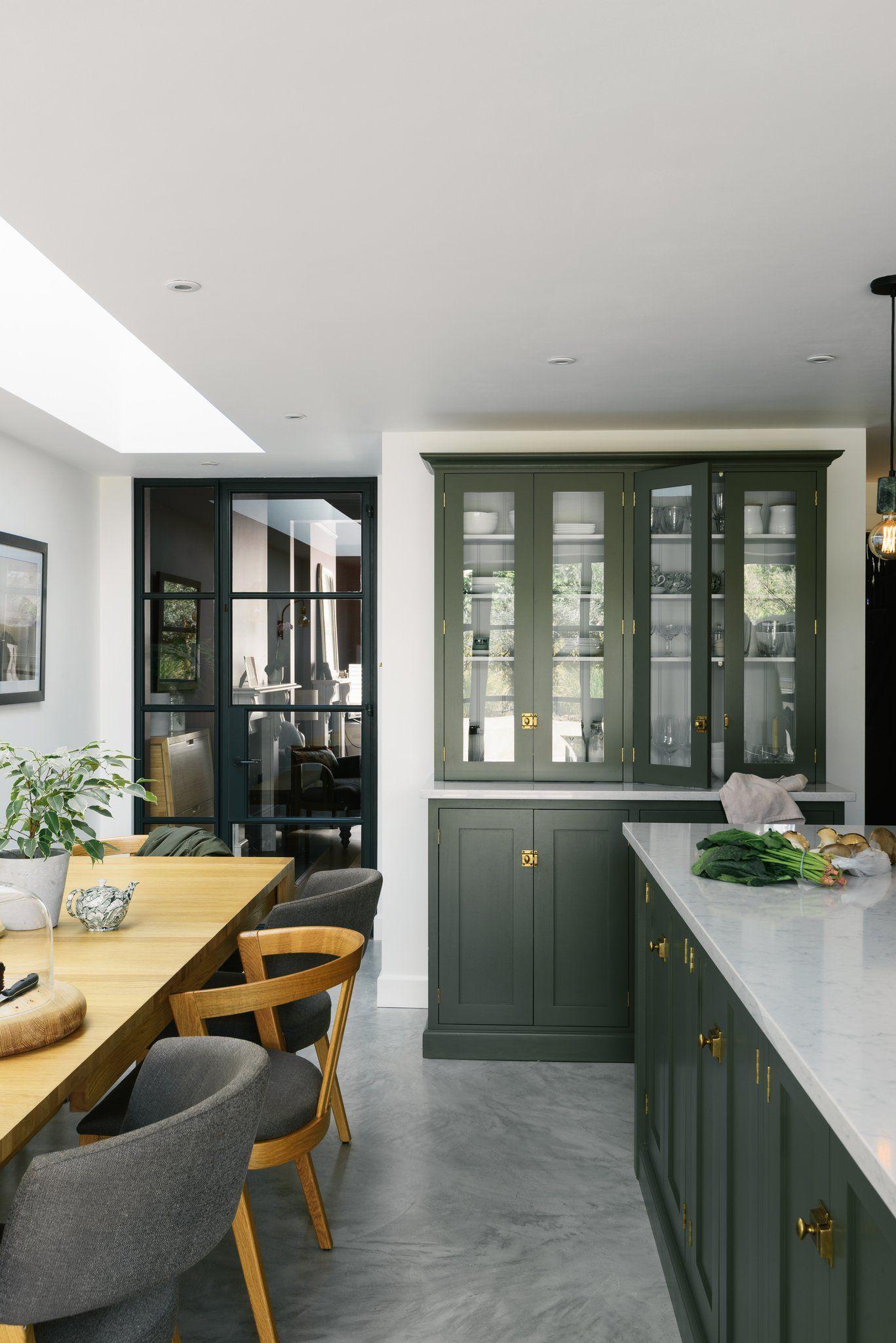 dark green kitchen with glassfronted upper cabinets
