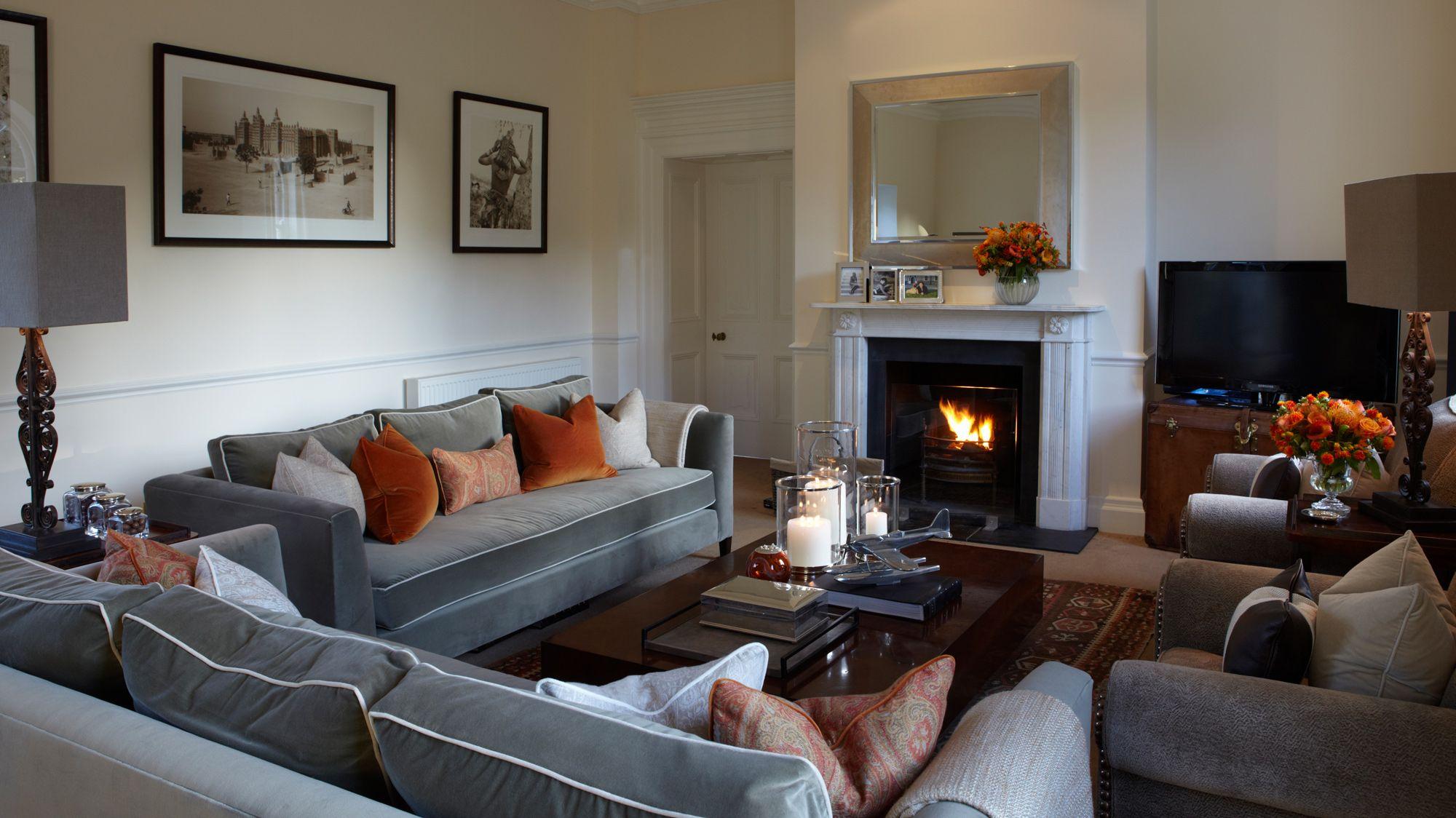 Grey velvet sofas with white piping & orange velvet pillows