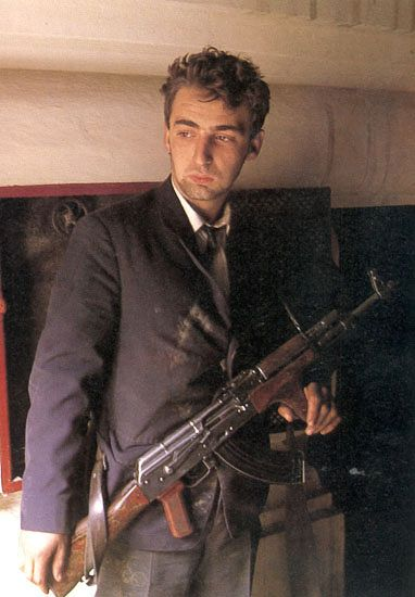 An anti-Ceausescu fighter from the Romanian Revolution armed with an AK-47, Romania - December, 1989. Dictator Ceasusescu and his wife were tried by a military panel and summarily executed in a schoolyard. A fitting ending for both for detroying their country.
