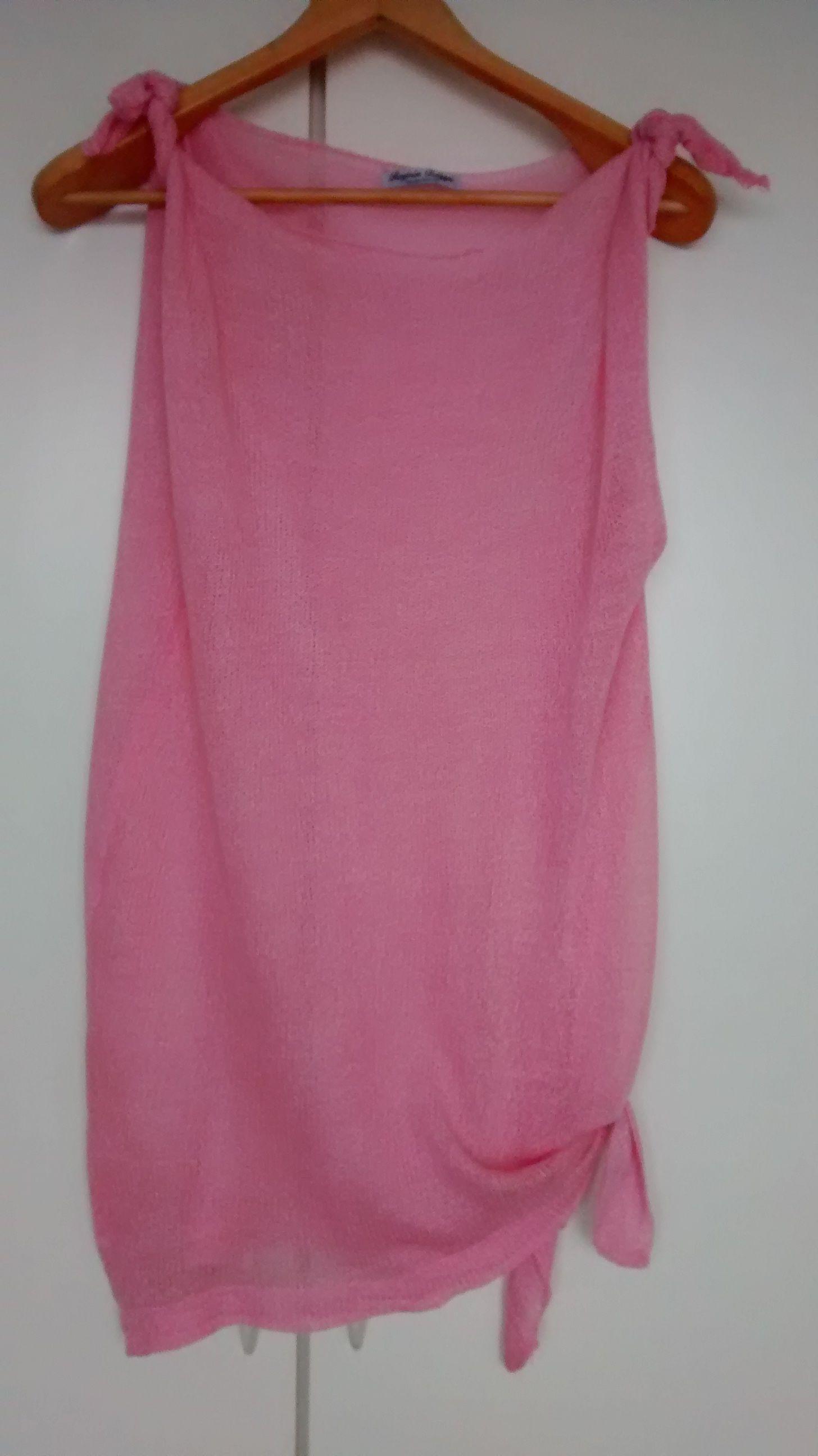 Fresquíssima saída de praia, cor rosa, em tricô à máquina, com graduação nos ombros e lateral com amarração.