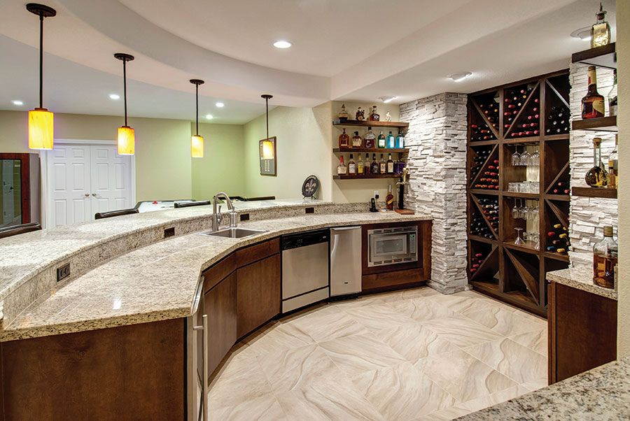 Curved bar topped with granite slab creates a large area for