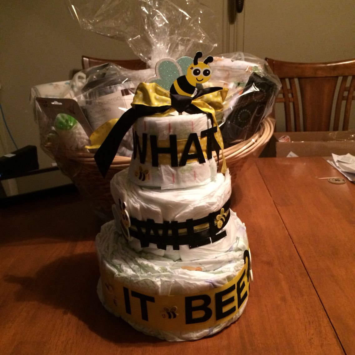 A diaper cake for a unisex baby shower with a gift basket