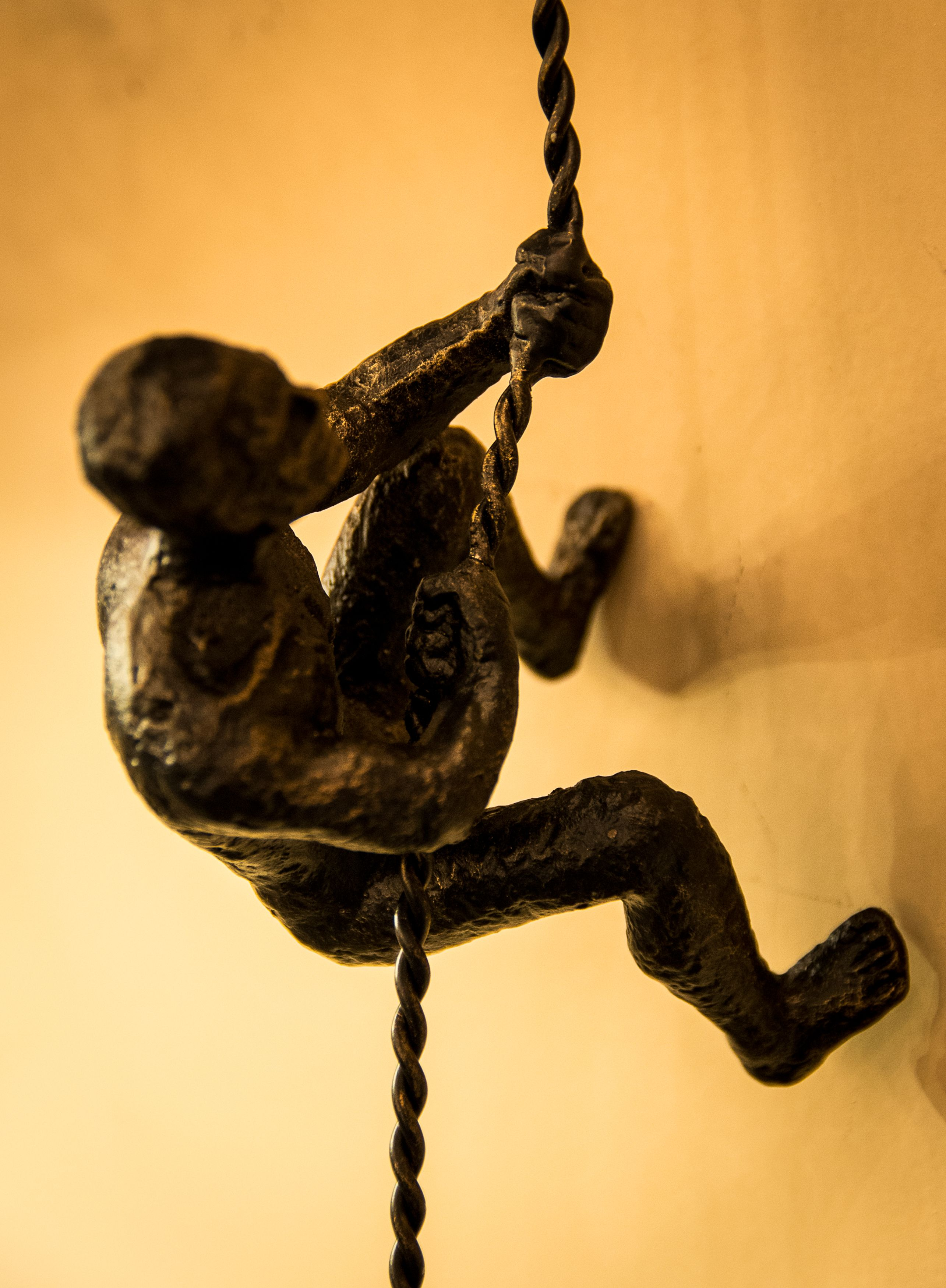 Bronze climbing man wall art. Whimsical man climbing up the wall on ...
