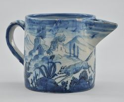 A Faience Milk Jug, Italian,18th Century. Earthenware handled jug with hand painting in blue glaze over light ground. Linear drawing of cherub, running fox and distant buildings. Approx. 5 1/2 inches tall x 8 inches in diameter