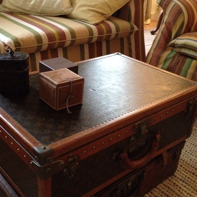 Antique Louis Vuitton suitcases used as side table