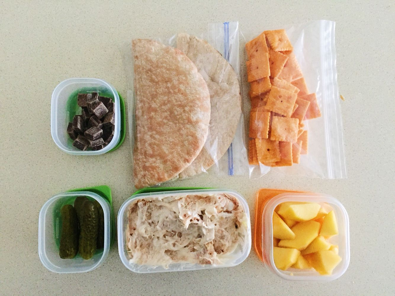 Cheezits, pita pockets, petite pickles, fresh peach slices, tuna salad, and 62% cacao dark chocolate squares.