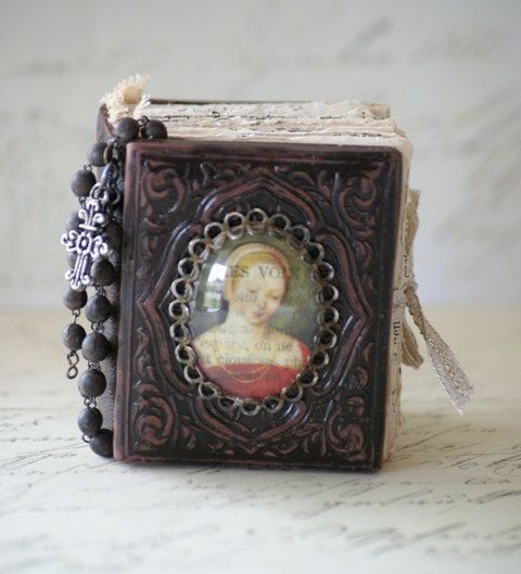 This book is modelled on an antique daguerrotype photo case from the 1800's. It is made from polymer clay, painted and aged.  The paper signatures are made up from various vintage text book papers.
