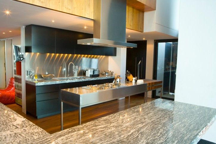 Moderne Küche mit Edelstahl-Insel, schwarze Schränke, harten ...
