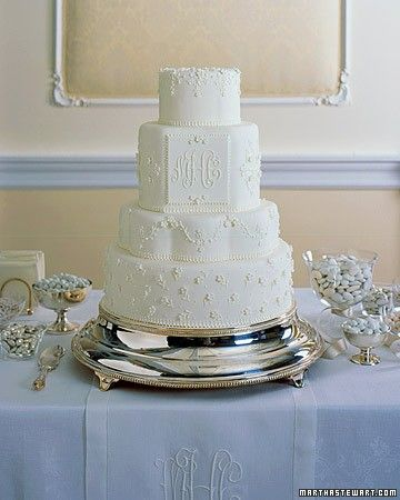 The delicate gum-paste flowers and royal-icing beading on this elegant cake evoke classic white-on-white embroidery. The ornate three-letter monogram was copied from the hemstitched runner.