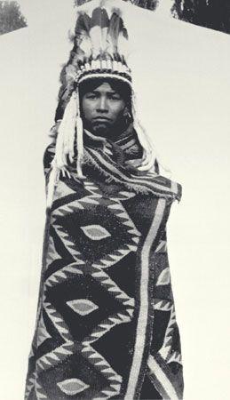 Jeune homme nlaka'pamux (thompson) emmitouflé dans une couverture en poils de chèvre et portant une coiffure ornée de plumes d'aigle, Colombie-Britannique, © MCC/CMC, J.A. Teit, 30991