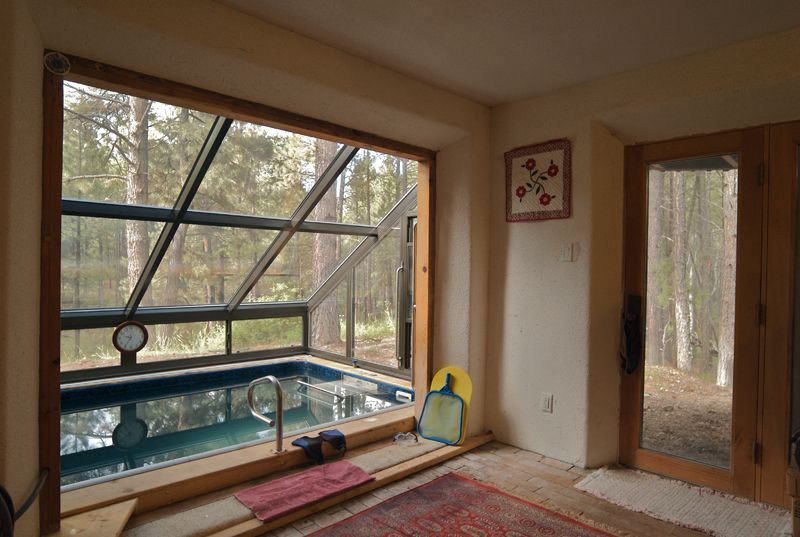 """Using water as a """"solar Mass"""" to trap heat.  A passive solar system.  also a sweet indoor outdoor pool."""