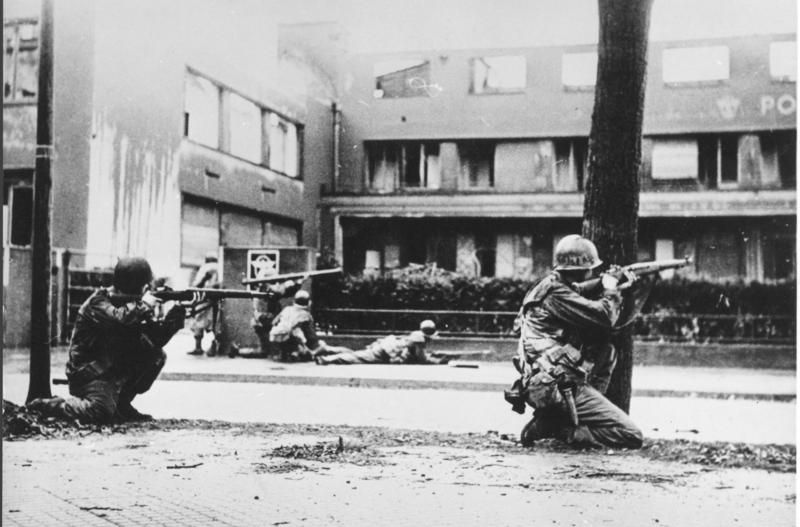 American soldiers take cover from German fire in the street. Mannheim, Germany. 29th of March 1945.