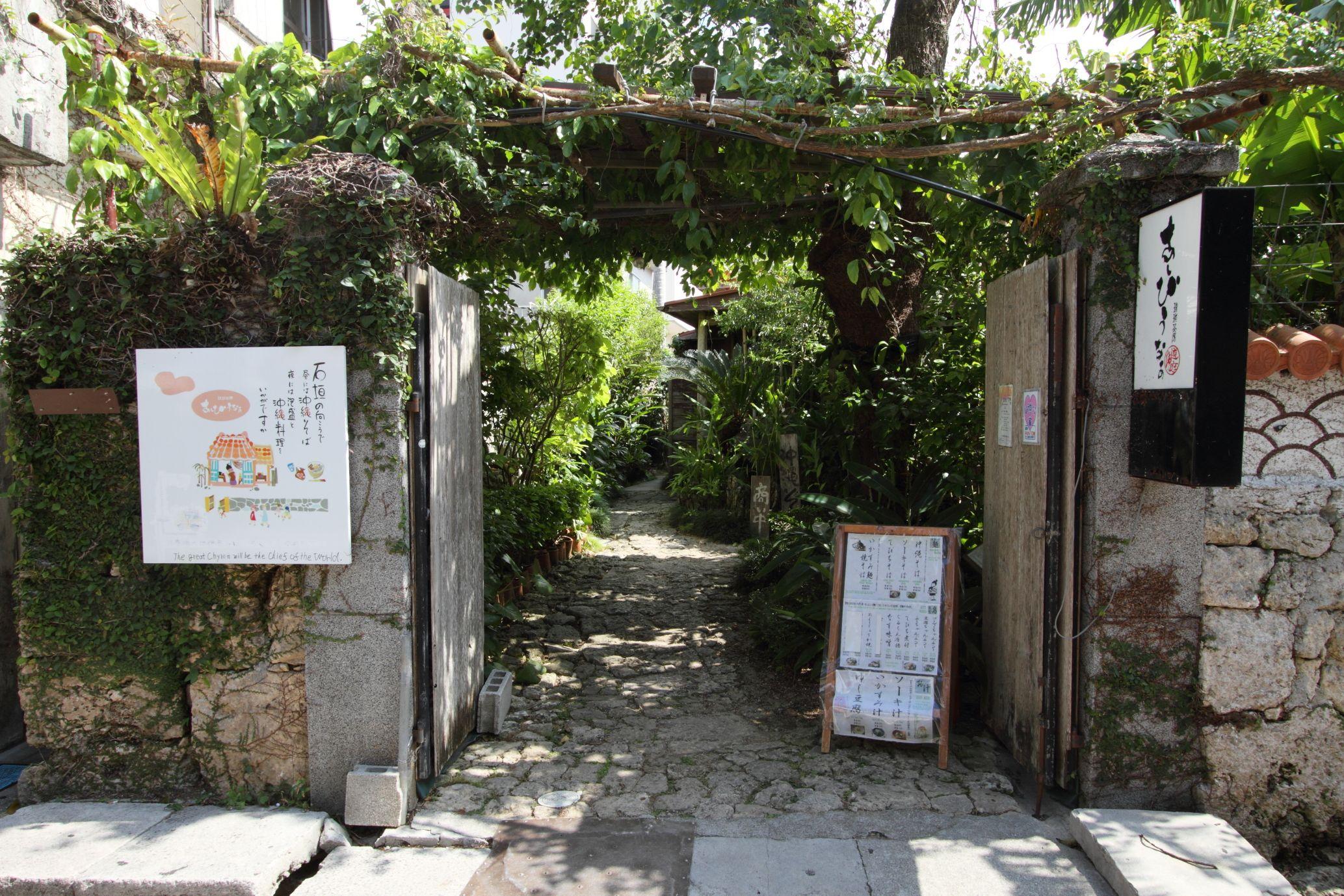 沖縄古民家で琉球伝統料理を提供している琉球茶房あしびうなぁ。庭を取り囲む縁側席からは、広い庭を一望できる。ランチは沖縄そばや沖縄の家庭料理を盛り込んだ定食を、夜は琉球料理と泡盛をの