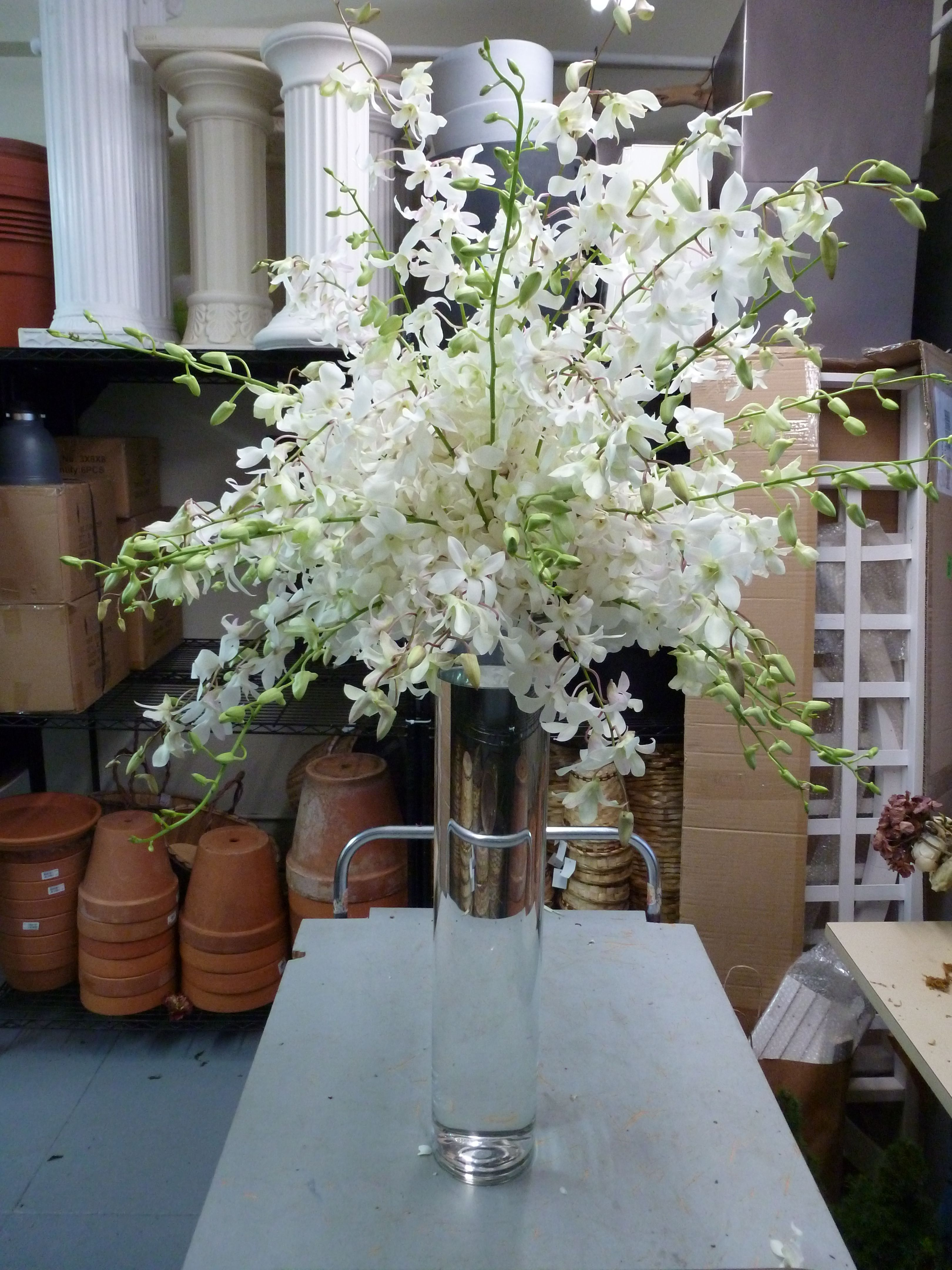 White dendrobium orchid spray resting atop a tall vase to for Flower sprays for weddings