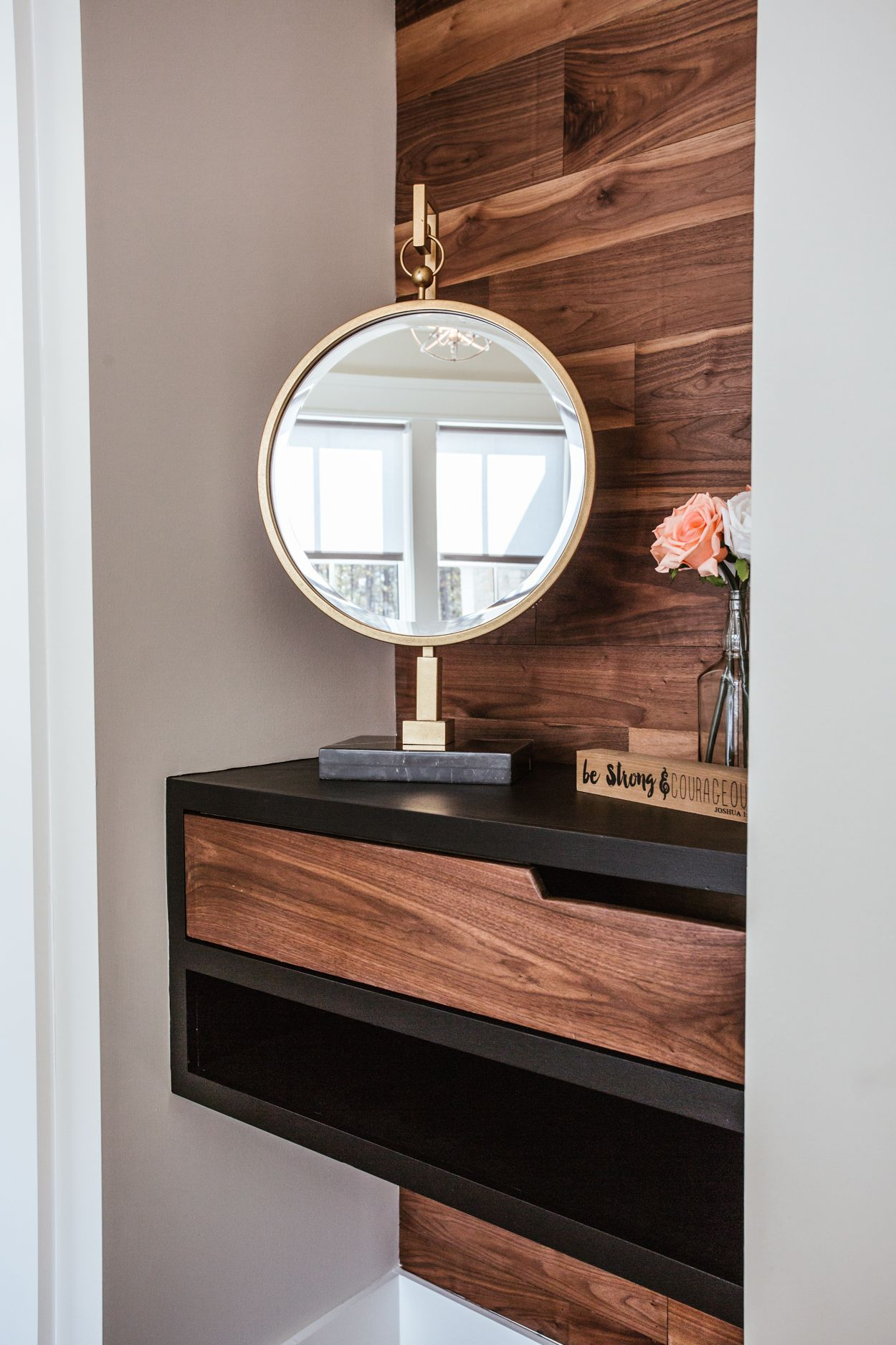 Builtin vanity with black walnut flooring on a wall and drawers