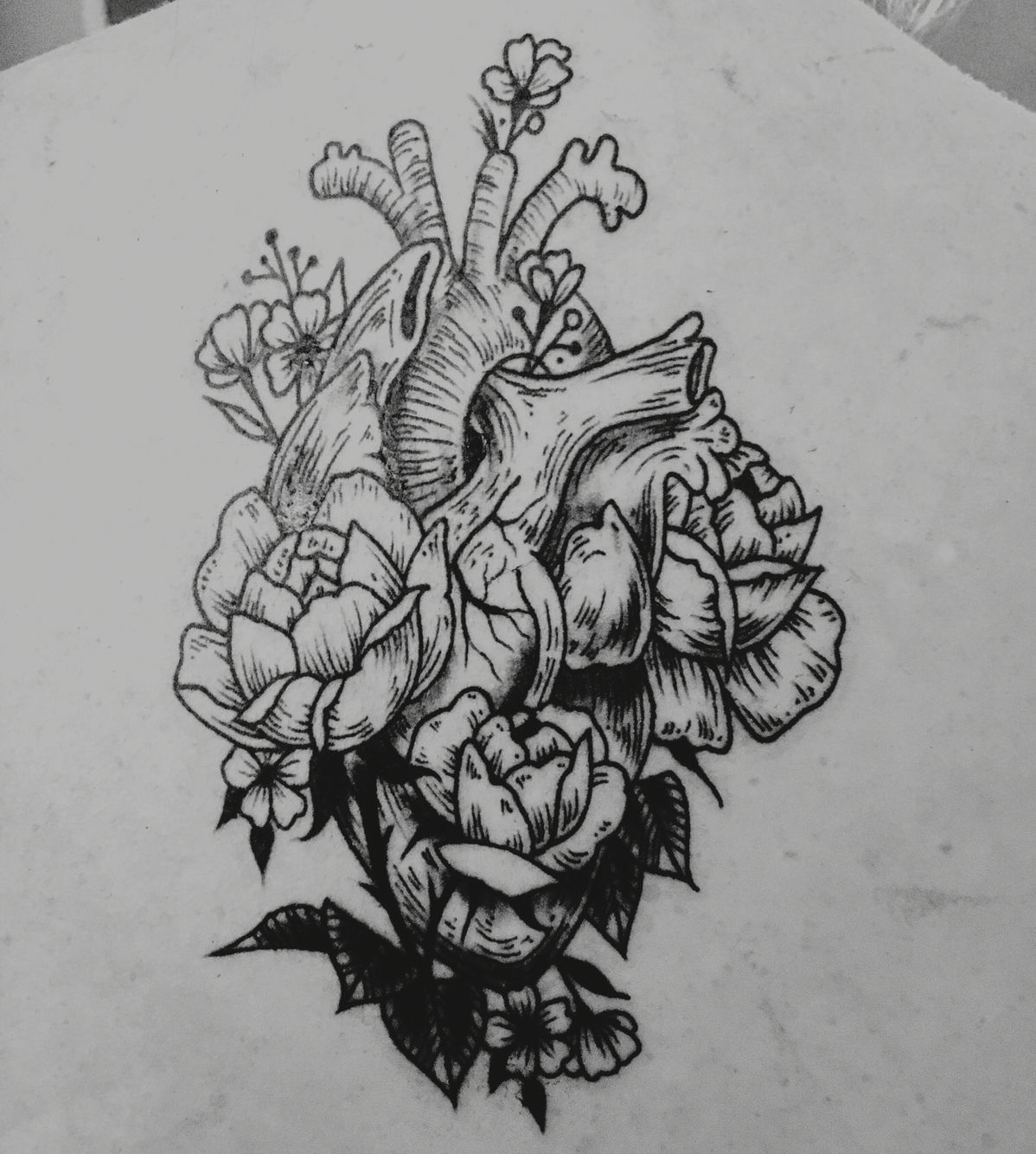Anatomical heart line art detail tattoo with floral
