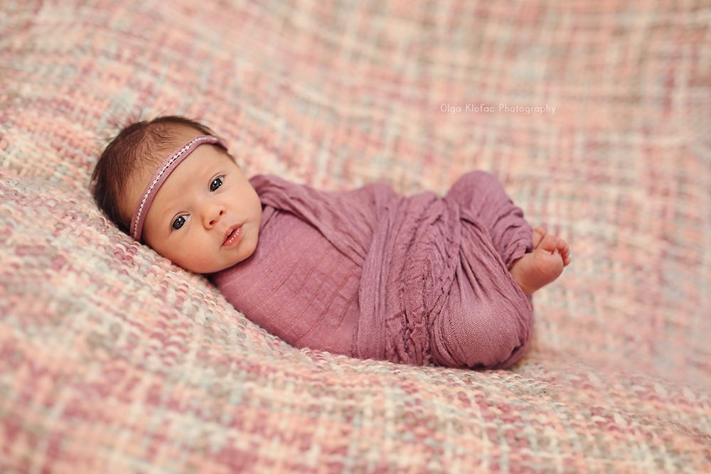 Newborn baby girl wearing purple headband and wrapped in purple scarf unique fine art baby portraits by olga klofac professional newborn photographer