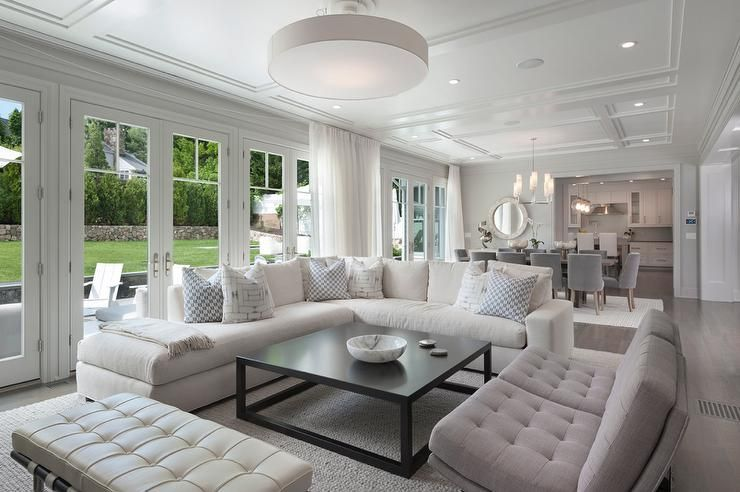 Chic Living Room Features A White Linen Sectional Lined With Blue Pillows  Facing A Black Coffee