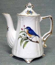 Victorian...Antique-styled...A little exotic...the bluebird perched on a single tree limb on a white background.  This is a conversation piece for a quaint tea party in The Hamptons. The azure bluebird is the state bird of both New York and Missouri.  The teapot is hand-decorated in the USA and made of fine porcelain.    2 Cup capacity