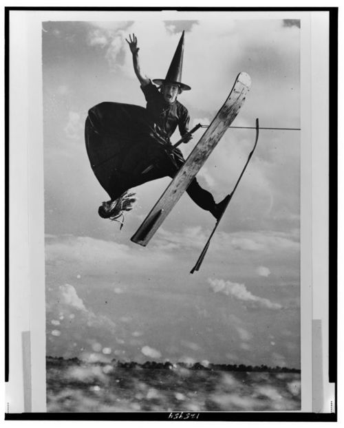 Full-length portrait of water ski champion Alfredo Mendoza skiing in witch's costume, holding broomstick, jumping in mid-air, Cypress Gardens, Florida. 1953. °