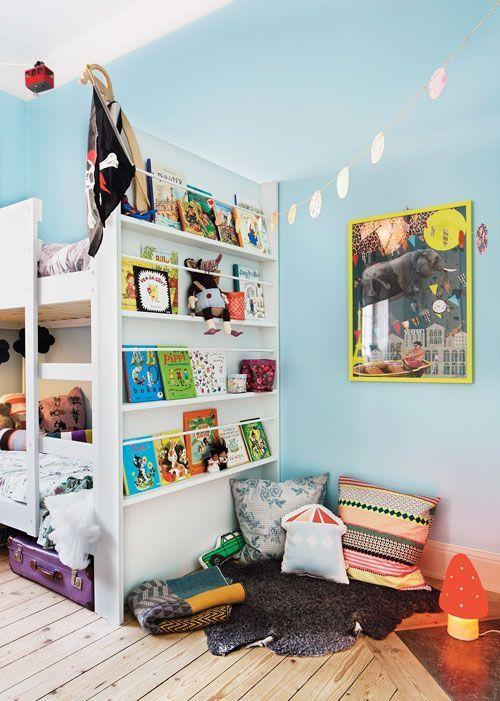 Estantes con libros y rincon lectura al pie de la litera