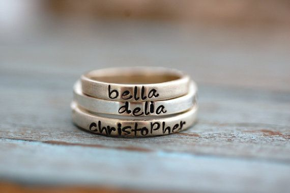 Hand-stamped stacking rings in sterling by SomethingAboutSilver, $28.00. Question is, what names/words would you have printed on them?