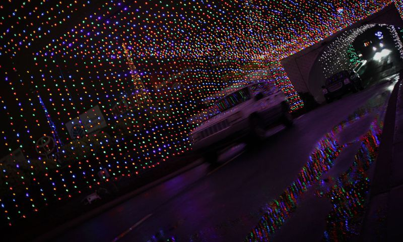 Charlotte Motor Speedway Christmas Lights.A Car Drives Through A Tunnel Of Lights During Speedway