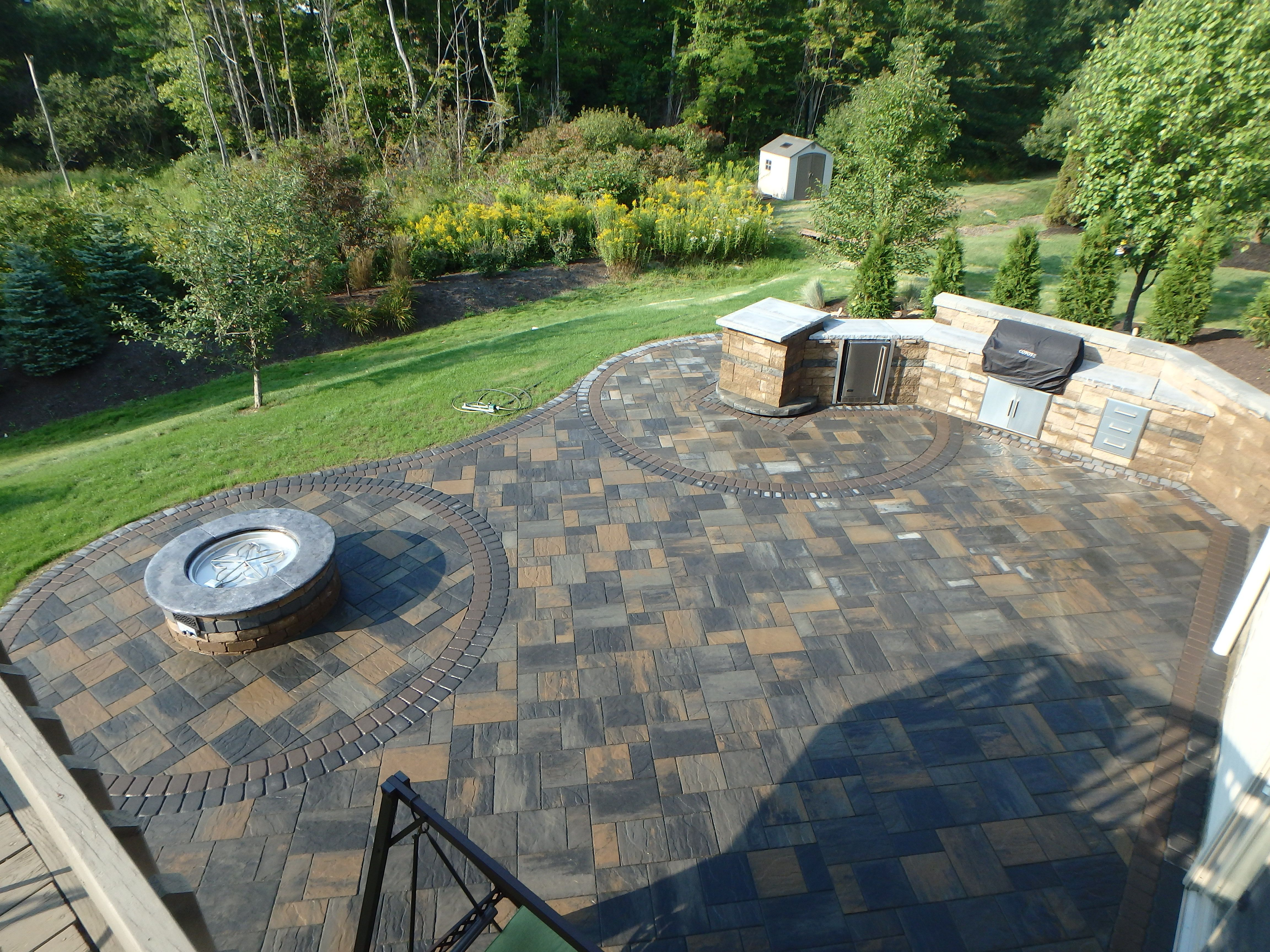 large paver patio with gas fire pit outdoor kitchen that has a