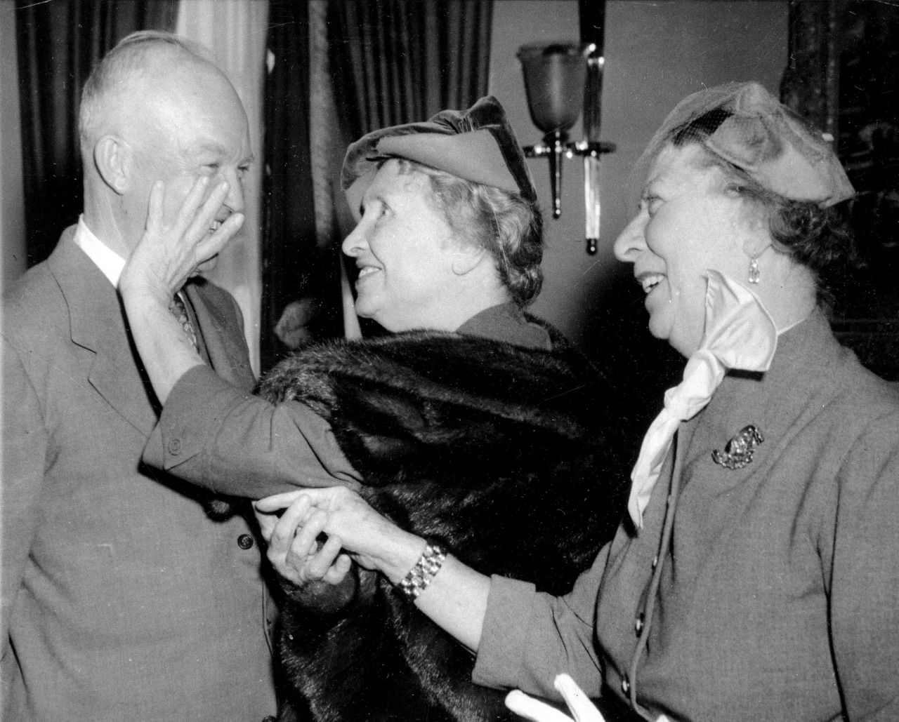 Helen Keller, 73, who is blind and deaf, guides her hand over U.S. President Dwight Eisenhower's face as her companion Polly Thomson communicates the President's comments by sign language on Keller's palm, November 3, 1953 ""