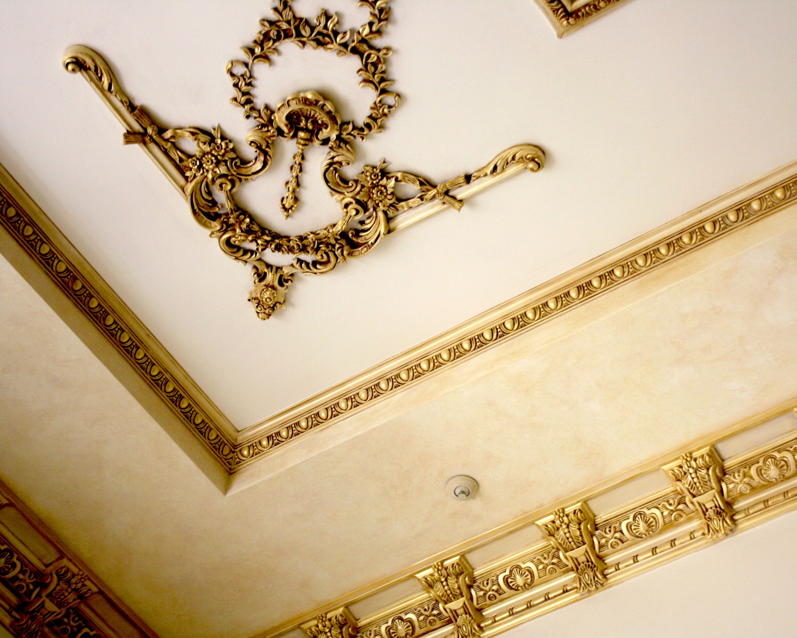 Ornate moldings are painted with an antique gold finish on Great ...