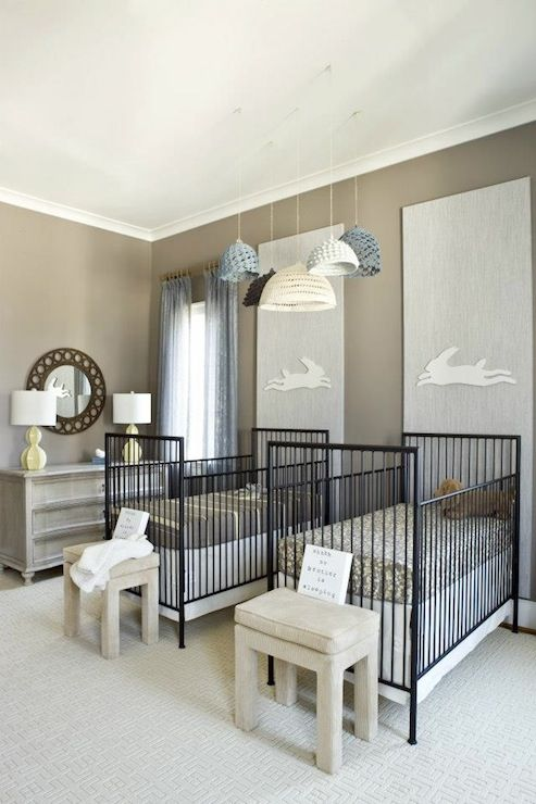 Adorable twin nursery with cluster of crocheted pendants over his and her twin nursery cribs filled with brown and yellow crib bedding and cream ottomans at foot off cribs. Chic nursery features bunny art on vertical gray panels over black modern cribs as well as round mirror over gray curved dresser with yellow table lamp on gray walls accented with blue drapes.