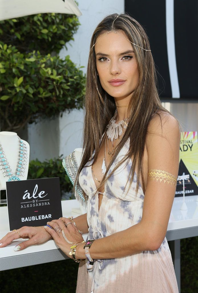 Stand out like Alessandra Ambrosio using lots of bling! Flash Tattoos, body jewelry, and shimmery eye makeup should do the trick. / Celebrity Beauty Inspiration From Coachella 2015