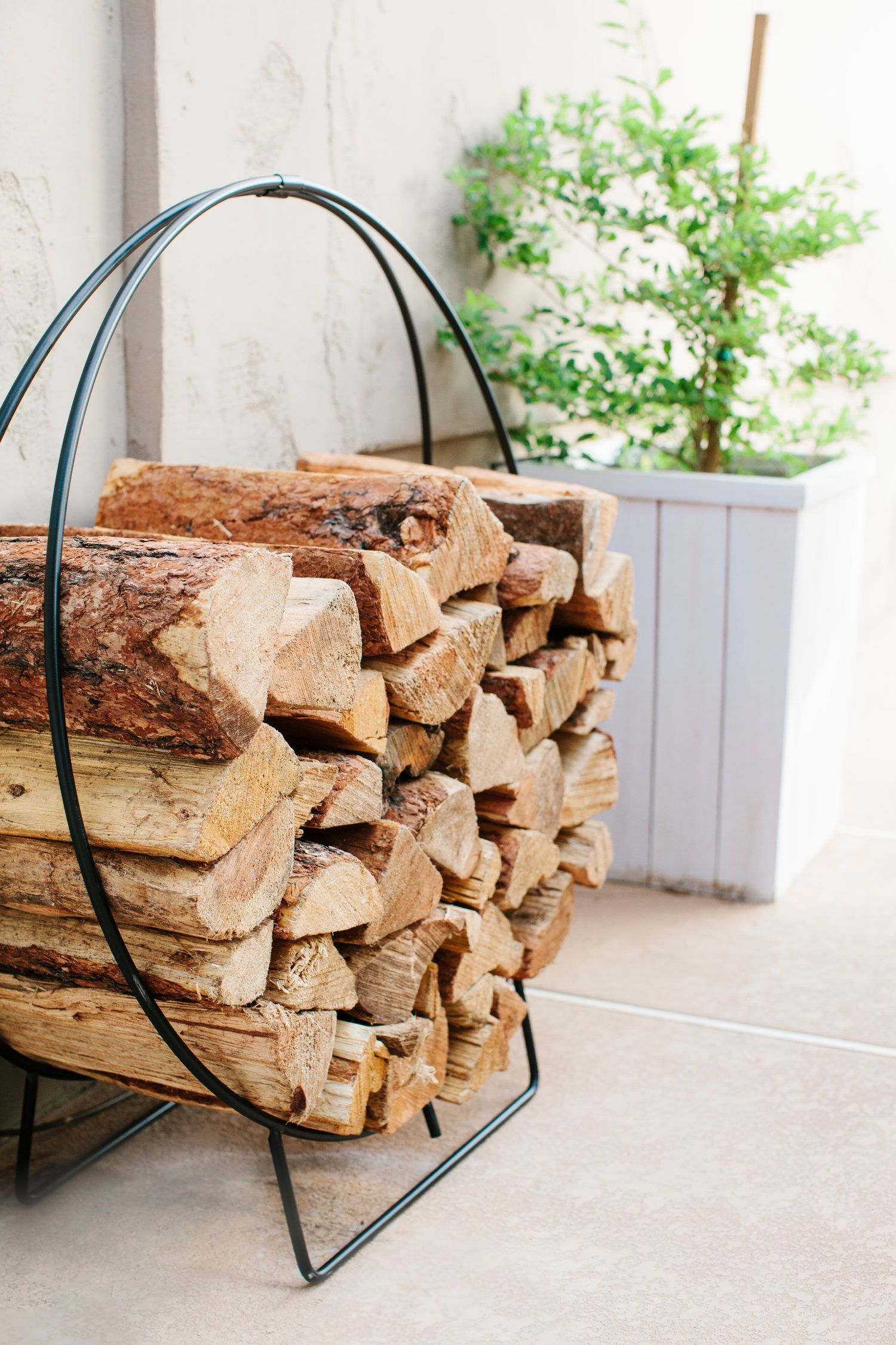 modern log hoops a great way to store firewood and add a lot of design interest to an outdoor space