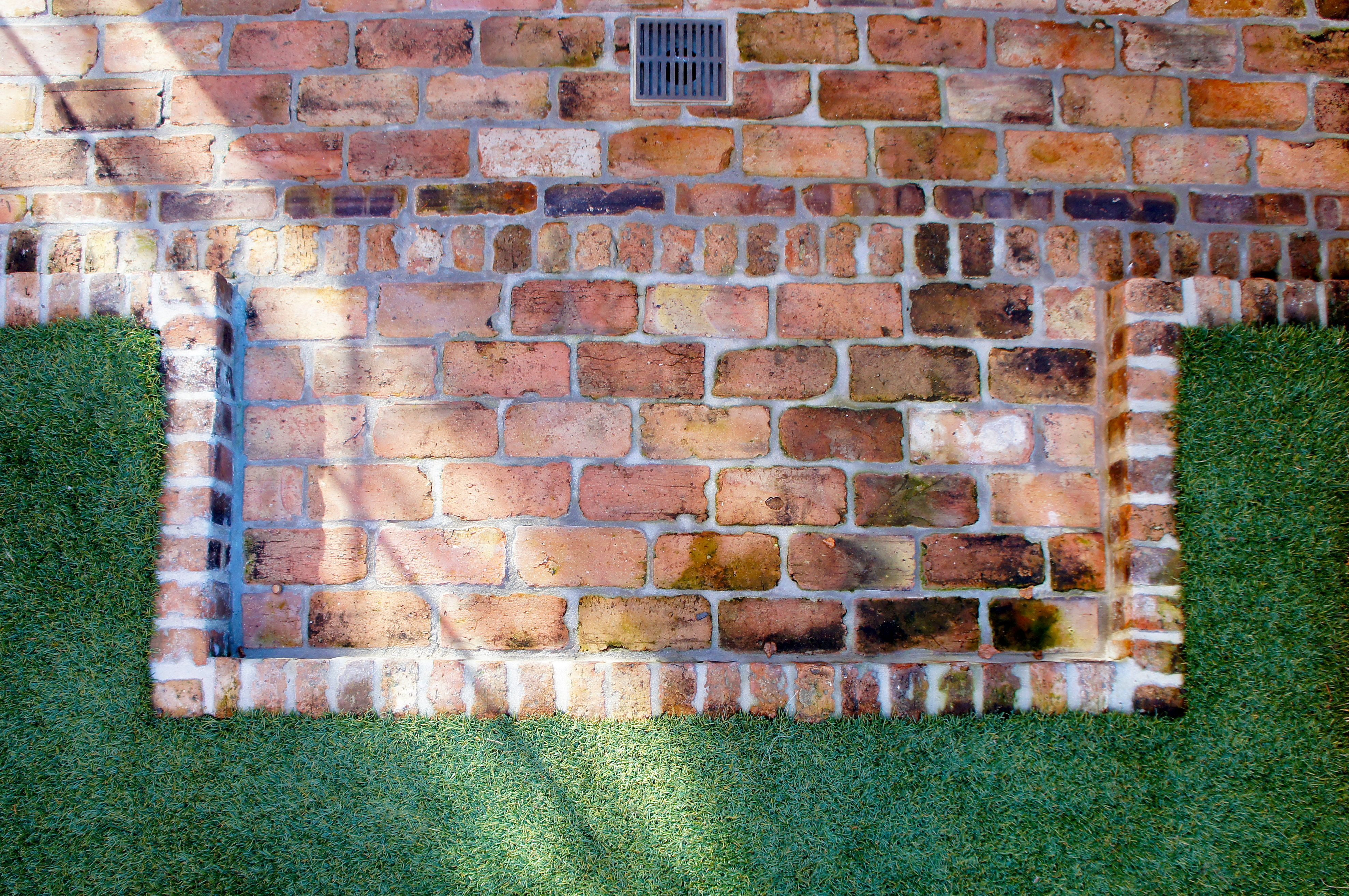 Brick design feature borders synthetic grass in english style