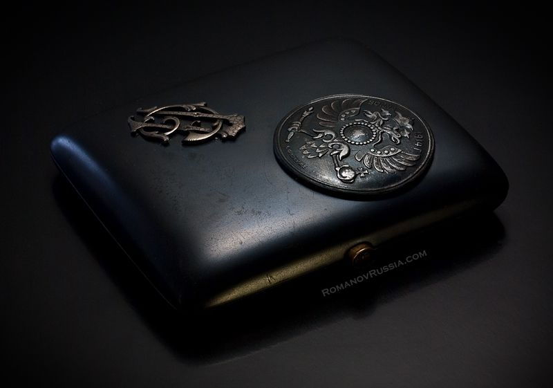 Important World War I Russian Imperial presentation GUN METAL cigarette case by Carl Faberge.  The lid is applied with a round gunmetal medallion and silver Cyrillic monogram ' СП '.  Apparently, this is the only known Faberge GUN METAL case with inscription WAR 1914.  $19,000.00