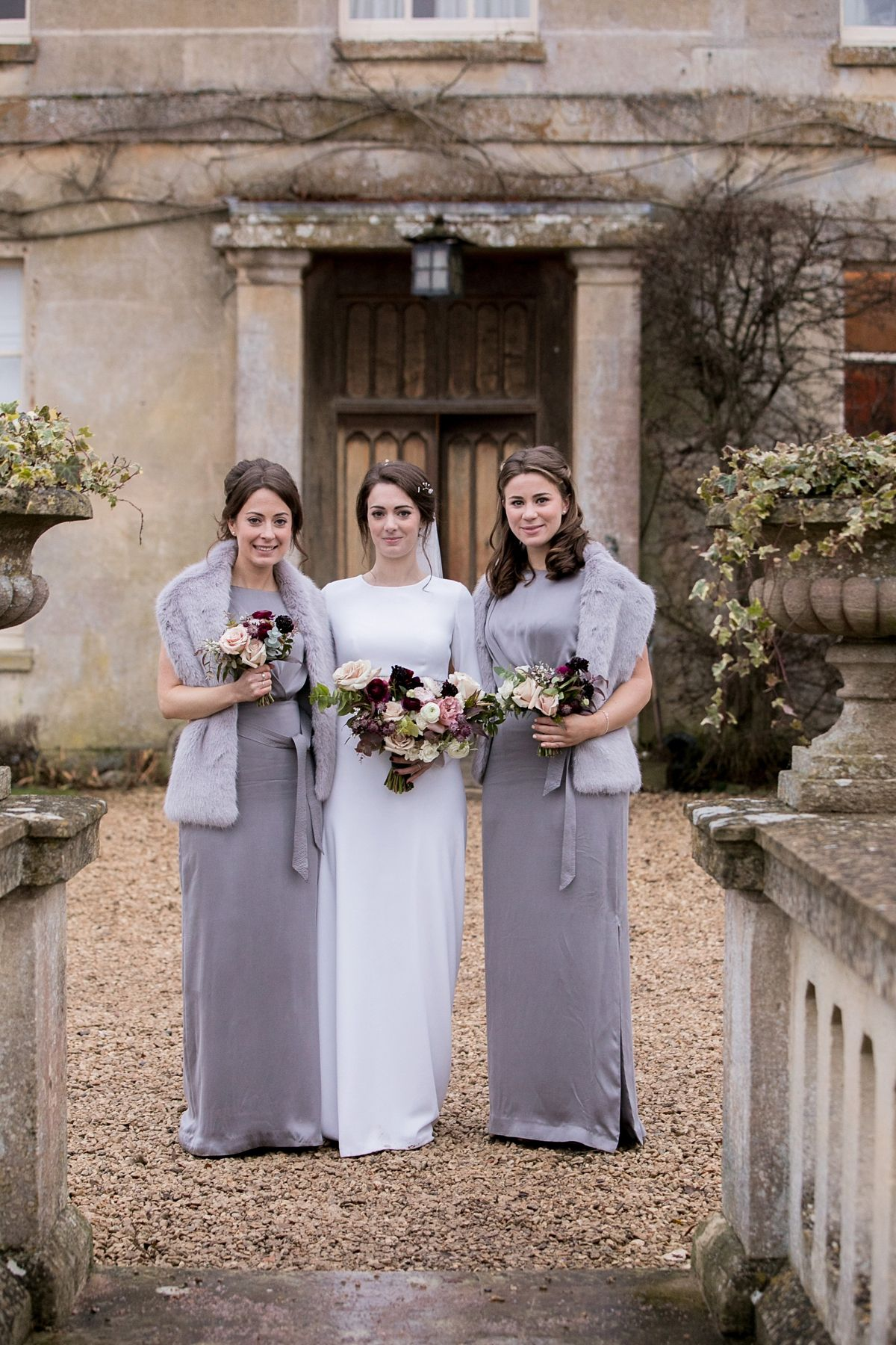 0d29c93631d2 Maids wear grey dresses and faux fur wraps for a Christmassy Winter Wedding  in Wiltshire. Images by Richmond Pictures