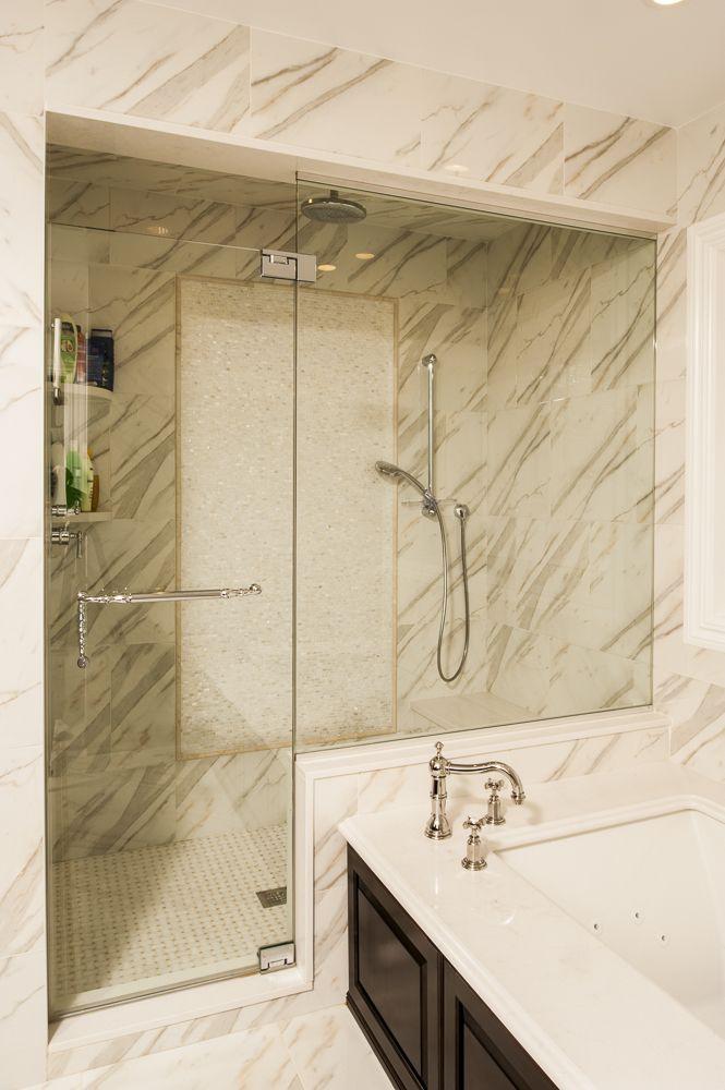 Walk in shower with shower bench and handheld shower. Frameless shower doors, Mosaic tile, and tub with tub deck #LongIslandBath #LongIslandLuxuryBath