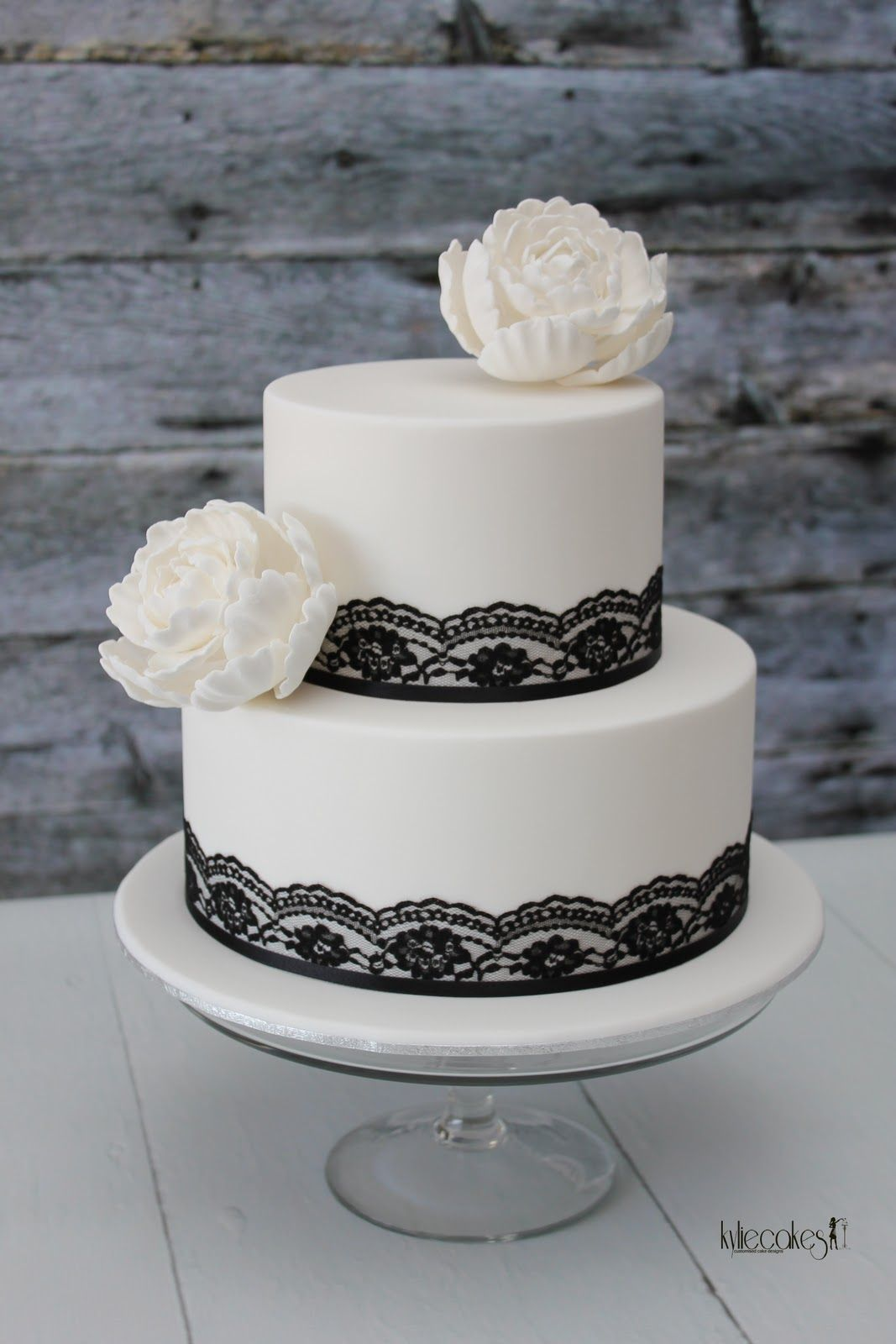 Four-tier black and white wedding cake with ribbons and crystals ...