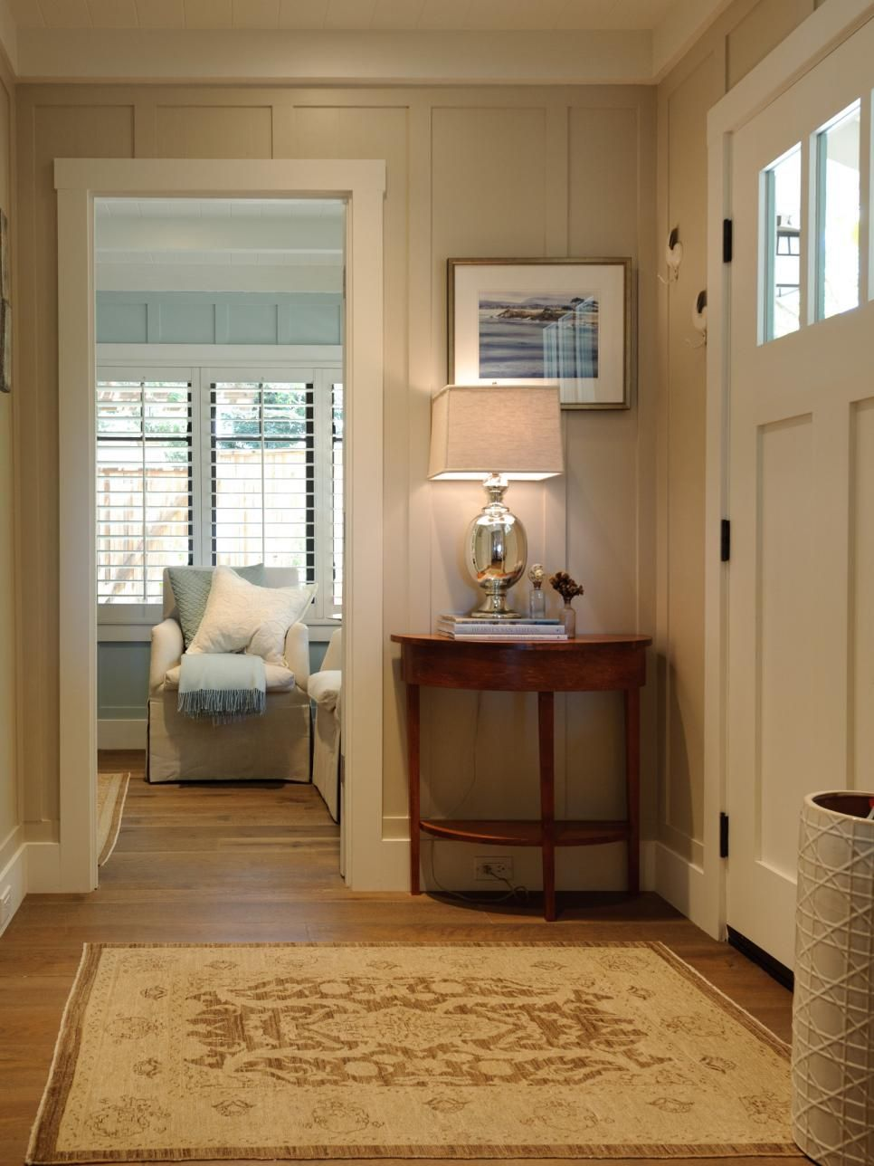 Soft taupe paneled walls and a neutral, traditional rug create a stylish entry in this casual, coastal home. The side table by the door provides an easy landing spot for keys, while the lamp on top means you never have to return home to a dark house. Board-and-batten-style walls add visual interest and texture to the space.