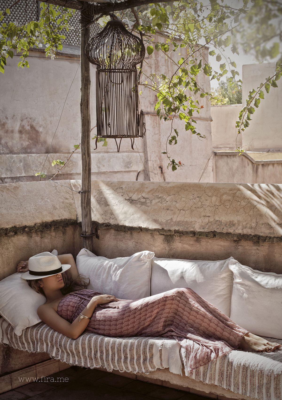 Una mujer tumbada en un diván, a la sombra, echándose una siesta