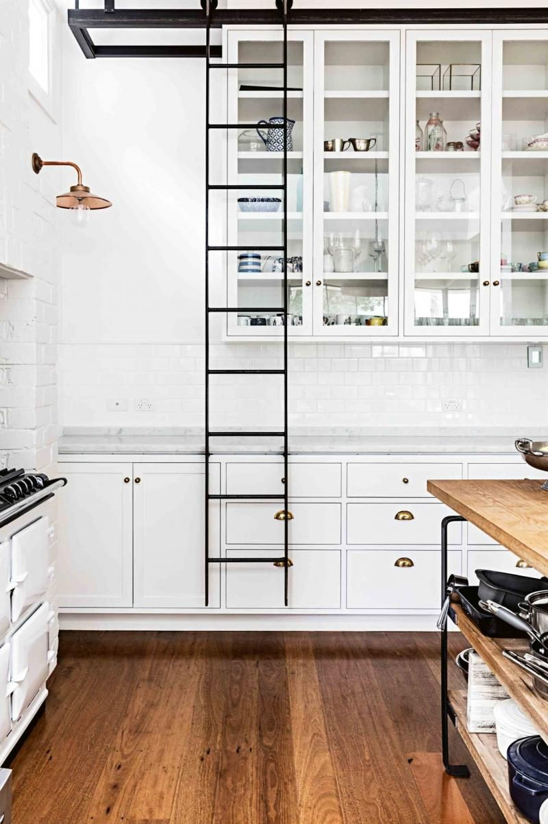 white kitchen with rolling ladder for easy access to tall cabinets ...