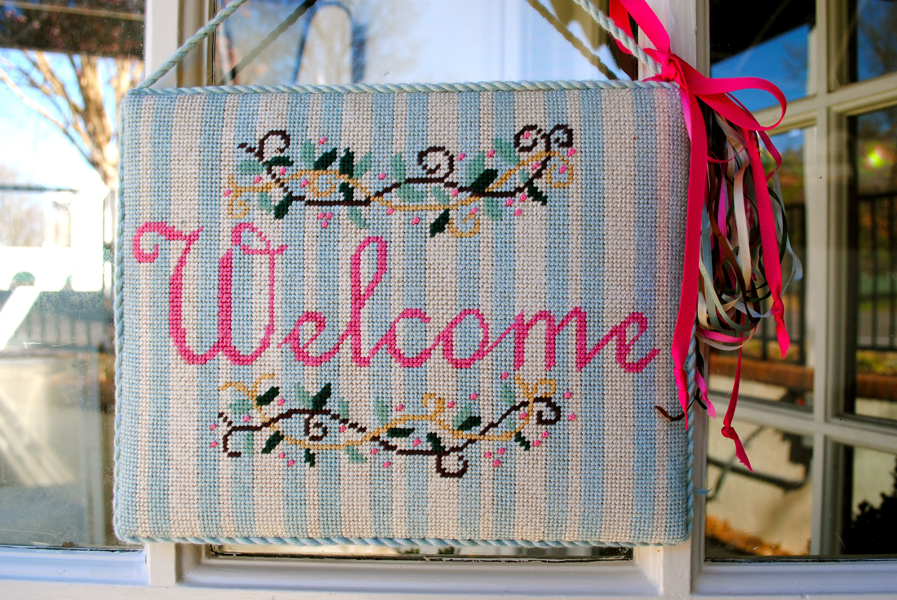 Sign by Patty Paints. Stitched by me. Hanging on the shop door at Adornment Needlepoint.